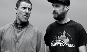 """Sleaford Mods Dance In The Road In New Music Video For """"Nudge It"""" Featuring Amy Taylor Of Amyl and the Sniffers"""